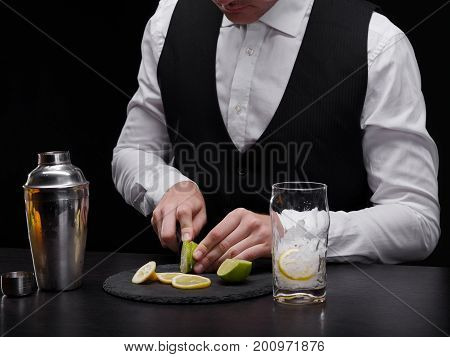 A classy barkeeper in a black and white suit making a fruity alcoholic beverage. A bartender cutting limes and lemons next to a glass with ice and a shaker on a bar counter on a black background.