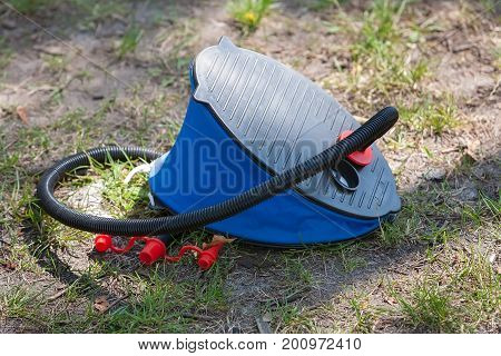 Summer day. Picnic near the lake and the river or the sea. In the frame a foot pump for an air mattress. Horizontal frame. Sunny day