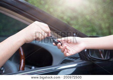 Closeup Male hand handing car keys to the woman.