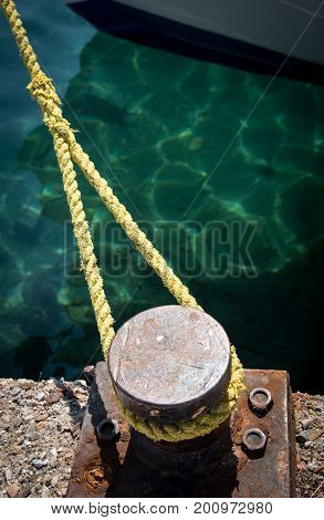 Metal bollard and rope securing a ship in the harbor
