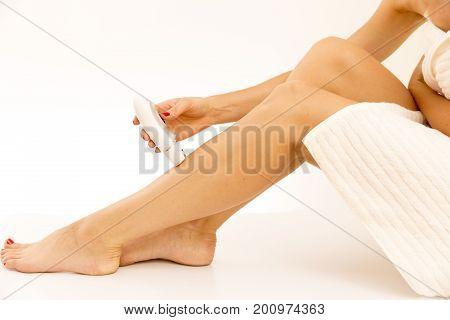 Beautiful female legs with the epilator isolated on white background