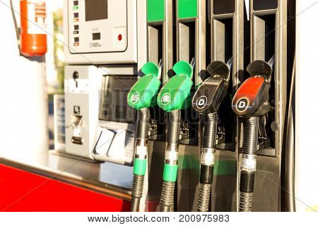 Colorful Petrol pump filling nozzles. Gas station in a service in daytime
