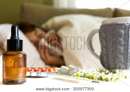 Pills camomile tea and homeopathic extract on table. Young woman lying on a bed covered with blanket blowing her nose in background