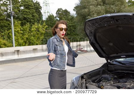 Confused young woman looking at broken down car engine on street