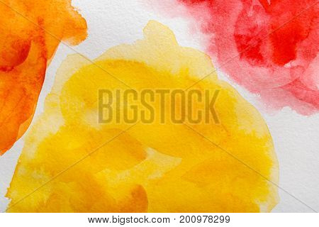 Abstract watercolor yellow, red and orange spot painted texture background.