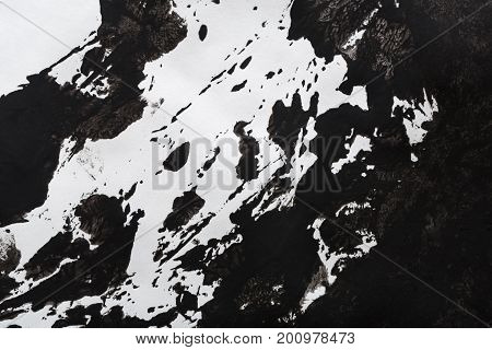 Abstract background with black watercolor handpainted spots on white paper. Black and white textured backdrop