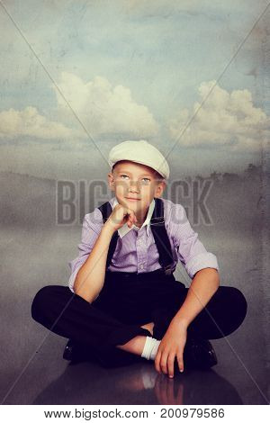 Old Fashioned Boy Sitting. Photo In Retro Style.