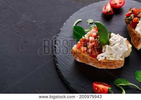 Italian appetizer on black slate background. Crusty bruschetta with concasse tomatoes, stracciatella cheese decorated with spinach. Delicious and healthy restaurant meals, copy space