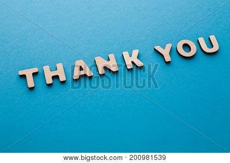 Phrase Thank You on blue background. Politeness, thanks, gratitude concept