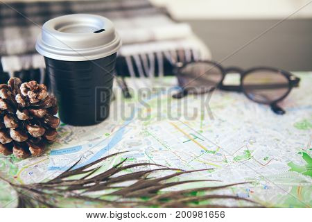 Traveler concept. Map, sun glasses, scarf and cup of take away coffee on the table. Traveling consent. Resting and making plans for new sign seeing points, looking at the map and drinking take away cup of coffee in the cafe