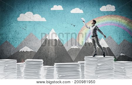 Man in casual wear keeping hand with book up while standing on pile of paper documents with drawn landscape on background. Mixed media.