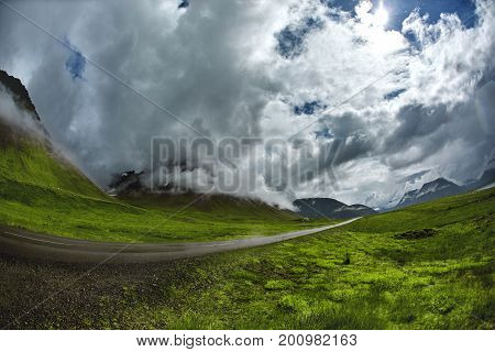 Travel to Iceland. A mountain road with fog and clouds to the town of Isafjordur and a view of the fjord after rain. focus on the road