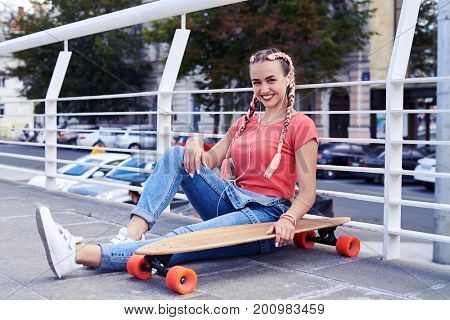 Wide shot of young woman relaxing while sitting under handrail with skateboard with copy space