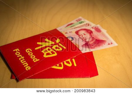 The red envelope or hong bao is used for giving money during the Spring Festival, or Chinese New Year in China and Taiwan. Envelope with the chinese words meaning Good fortune on it, and yuan bills.