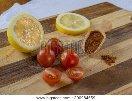 Three And Two Half Of Cherry Tomatoes With Half Lemon Lemon Slice And Scoop With Red Pepper Spice On
