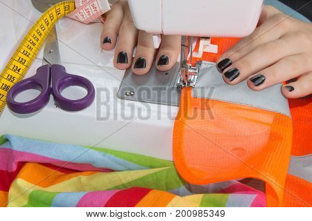 Sewing Process the sewing machine sew women's hands sewing machine. sewing machine and female scissors. Woman's Hand Sewing Quilt