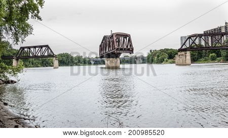 horizontal image of a train drawbridge that is open across the lake under a cloudy rainy sky in the summer time.