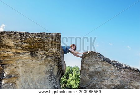 horizontal image of a caucasian woman lying on top of a tall sandstone rock formation and leaning forward to touch the formation next to it on a beautiful summer day.
