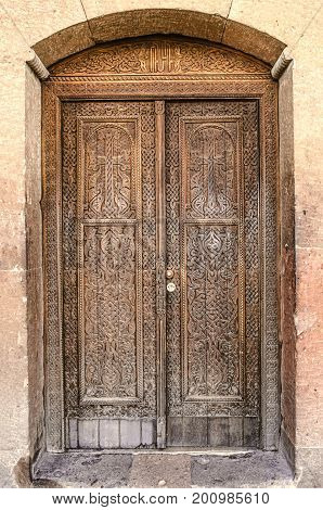 Closed entrance wooden door with cross in the Church of the Martyr St. Hripsime in Echmiadzin