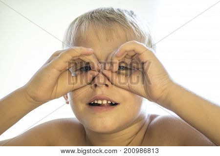 Little Boy Is Looking Through Binoculars On A White Background