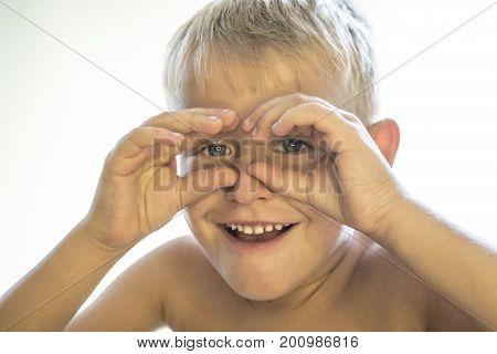 Little Boy Is Looking Through Binoculars On A White Background