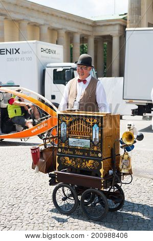 Berlin Germany - May 31 2017: organ grinder man with musical box in city on sunny day. Street music and entertainment concept. Summer vacation and lifestyle