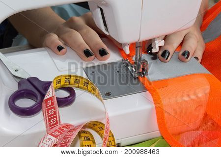 Woman hand on sewing machine.Dressmaker work on the sewing machine. Hobby sewing fabric as a small business concept. Female tailor threading leather material on sewing machine