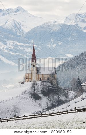 The church of St. Pankraz in Uderns Zillertal valley surrounded by fog and snow with Alps mountains in the background in a landscape on a white winter morning in Austria.
