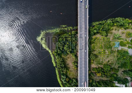 Aerial view of the bridge and the road over the Dnepr River over a green island in the middle of the river. Kiev, Ukraine