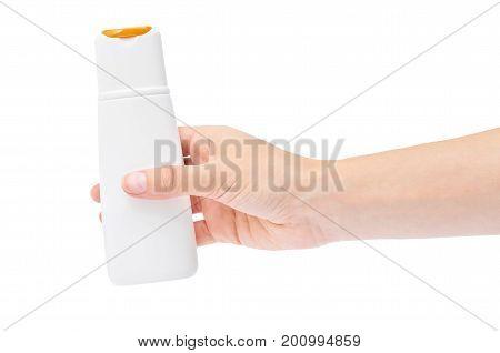 Hand holding shampoo bottle isolated on white background.