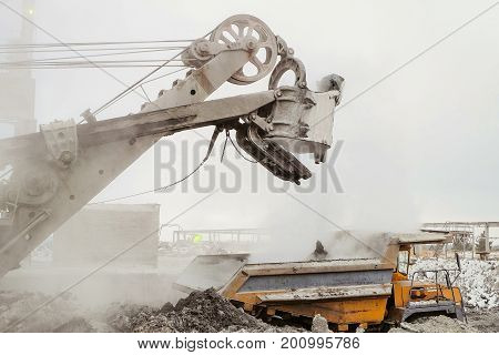 Excavator loading into a big mining dump truck. Work in heavy industry.