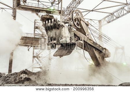 Large bucket powerful excavator in the hot dusty fog of heavy mining industry. Spectacular effective views work of a heavy digger closeup.