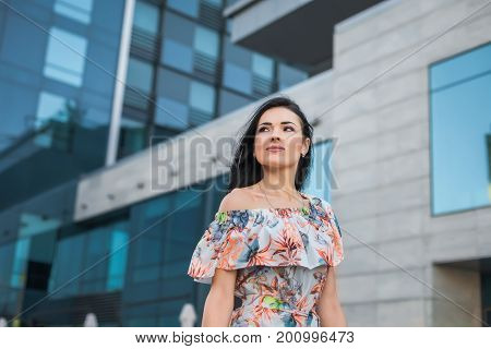 Young atractive beautiful brunette girl in the street wearing in white dress with flower pattern on the background of skyscraper