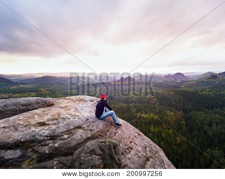 Hiker Man On Cliff. Tourist In Red Cap, Black Sweatshirt And Jeans Sit On Sharp  Mountain Cliff Abov