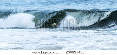A wave engulfs a surfer as it breaks on top of him in the early evening at Robert Moses State Park in mid August.