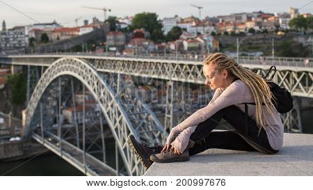 Young female sitting on the top observation deck on Douro river, overlooking bridge Dom Luis I, Porto, Portugal.