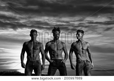 men or bodybuilders in jeans athlete people with sexy muscular torso six packs abs biceps triceps outdoors in sunset sky black and white