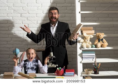 Girl And Her Father In Classroom On White Brick Background