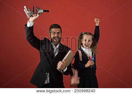 Kid And Dad Hold Microscope, Book And Stationery.