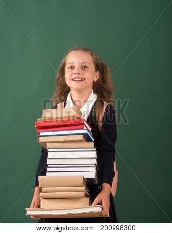 Schoolgirl With Smiling Face Holds Huge Pile Of Books