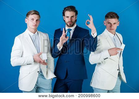 Manager with beard showing ok hand gesture. Men wearing formal suits. Business ethics and information concept. Businessmen showing blank cards. Group of people posing on blue background.