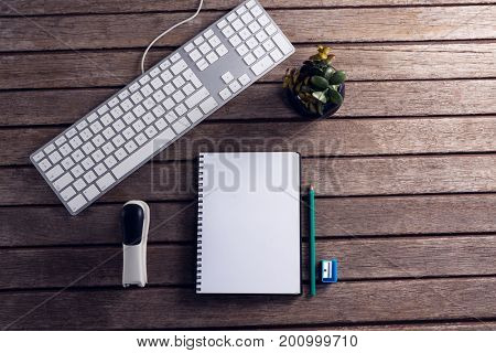Overhead of keyboard, diary, pot plant, stationery and stapler on wooden table