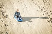 thrill-seeking young child riding a board down a sand dune hill having fun playing outdoors while on vacation. Cute boy Living life to its fullest poster
