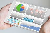 Hand holding modern tablet or mobile device with analytics dashboard for sales, marketing, accounting, controlling department to check revenue, sales and business KPIs poster