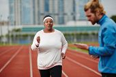 Young obese woman taking part in running marathon poster