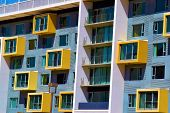 Contemporary style highrise residential building with colorful windows taken in an urban neighborhood poster
