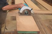 Electric circular saw against sawdust is cut a piece of wood by hands of senior carpenter in carpentry woodshop. poster