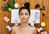 Relax at spa. Portrait of woman patient in ayurveda wellness center lies on wood with aroma spa accessories. Young beautiful indian girl with ideal clean skin rests with closed eyes in beauty parlor. poster