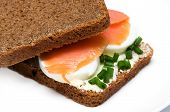 A sandwich with smoked salmon eggs and onion on a white plate poster