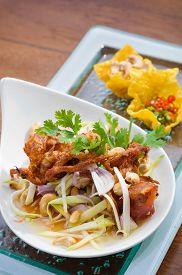 Thai spicy salad with deep fried soft shell crab and sliced green mango Yum Pu Nim in Thai cuisine